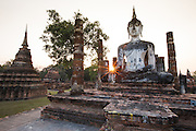 Temple ruins and a reconstructed Buddha statue at the ancient complex of Sukothai, Thailand