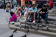 With many people and families staying in the UK for their Summer break during the school holidays, a large number of domestic tourists, who may normally have been travelling abroad, have decended on the capital to see the sights, as seen here as two men feed the pigeons in Piccadilly on 10th August 2021 in London, United Kingdom. Following the Coronavirus / Covid-19 health scare of the last two years, and with some travel restrictions still in place, more people have chosen a staycation which is a holiday spent in ones home country rather than abroad, or one spent at home and involving day trips to local attractions.