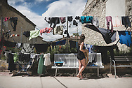 Lia, from Germany, inspects drying laundry outside an albergue in Hontanas, Spain. (June 15, 2018)<br />