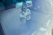 Image of checkered flag baby shoes inside a VW Beetle at the Bugin in Fontana, California, America west coast by Randy Wells