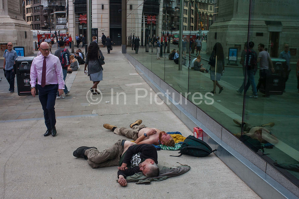 A successful businessman looks with pity at two men passed-out and sleeping on the ground near Pudding lane, the location of the Great Fire of London 1666, on 13th September 2016, in the City of London, England.
