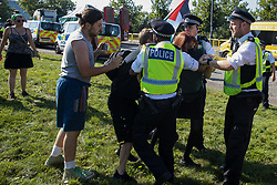 London, UK. 8th September, 2021. Metropolitan Police officers restrain human rights activists trying to stop a convoy of trucks delivering military equipment to ExCeL London for the DSEI 2021 arms fair. The third day of week-long Stop The Arms Fair protests outside the venue for one of the world's largest arms fairs was themed around demilitarising education.