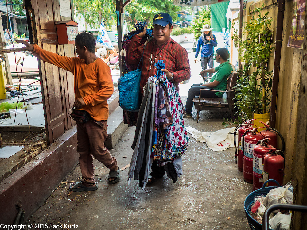 21 SEPTEMBER 2015 - BANGKOK, THAILAND: A door to door clothing vendor walks past a demolition crew tearing down a home near Wat Kalayanamit. Fiftyfour homes around Wat Kalayanamit, a historic Buddhist temple on the Chao Phraya River in the Thonburi section of Bangkok are being razed and the residents evicted to make way for new development at the temple. The abbot of the temple said he was evicting the residents, who have lived on the temple grounds for generations, because their homes are unsafe and because he wants to improve the temple grounds. The evictions are a part of a Bangkok trend, especially along the Chao Phraya River and BTS light rail lines. Low income people are being evicted from their long time homes to make way for urban renewal.    PHOTO BY JACK KURTZ