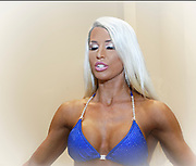 A woman prepares for a bikini competition closes her eyes in deep concentration.