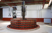 In the winery: a traditional, round, vertical, basket wine press with the hydraulic machinery in the background, Champagne Jacquesson in Dizy, Vallee de la Marne, Champagne, Marne, Ardennes, France