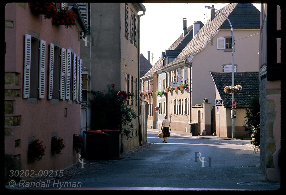 Woman with bread basket walks along main street in early morn sun; town of Eguisheim, Alsace. France