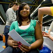 Nederland Helmond 2 maart 2009 20090302 Foto: David Rozing .Start vaccinatie tegen baarmoederhals kanker.3000 meiden tussen 13 - 16 jaar zijn opgeroepen om zich te laten inenten in sporthal City hal. .Vaccination for young girls, age 13-16, to prevent cancer of the cervix / neck of the womb. vaccine, vaccinations, vaccines, immunity, desease, deseases, preventing, prevention, shot, shots, girl, youth, ..Deze inenting zit vanaf 2009 in het Rijksvaccinatieprogramma (RVP). Vandaag begint een eenmalige actie waarbinnen meisjes die dit jaar 13 tot en met 16 jaar worden zich kunnen laten vaccineren. In september starten de reguliere inentingen binnen het RVP..De GGD'en verzorgen de inteningen. Een volledige inenting tegen baarmoederhalskanker bestaat uit 3 prikken. De meisjes krijgen deze verdeeld over een half jaar. vaccinatie tegen baarmoederhalskanker..Inenting in Rijksvaccinatieprogramma ?Vanwege de gezondheidswinst voor vrouwen is inenting tegen baarmoederhalskanker vanaf 2009 opgenomen in het RVP. Binnen het RVP krijgen meisjes de inenting steeds op de leeftijd van twaalf jaar. Vanaf september 2009 krijgen meisjes die op of na 1 januari en voor 1 september 2009 deze leeftijd bereiken een vaccinatie. .Baarmoederhalskanker krijg je alleen na een infectie met het humaan papillomavirus, kortweg HPV. De inenting beschermt tegen twee typen van het HPV-virus (HPV 16 en 18) die samen 70% van alle gevallen van baarmoederhalskanker veroorzaken...Foto: David Rozin