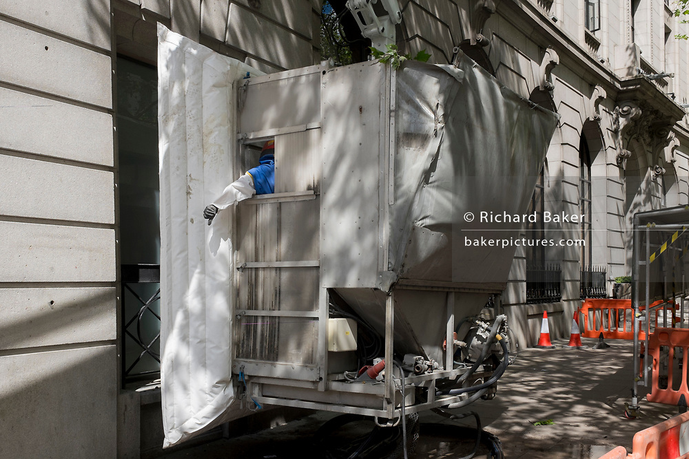 A machine operator gives the standard hand signal to a crane driver from inside enclosed equipment cleaning the stone work surfaces of an address in Aldwych WC2, on 2nd May 2019, in London, England.