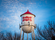 """Water tower in Frisco, Texas. Frisco is a city in Collin and Denton counties in Texas. It is part of the Dallas-Fort Worth metroplex, and is approximately 25 miles from both Dallas Love Field and Dallas/Fort Worth International Airport. Since 2003, Frisco has received the designation """"Tree City USA"""" by the National Arbor Day Foundation. When the Dallas area was being settled by American pioneers, many of the settlers traveled by wagon trains along the old Shawnee Trail. This trail was also used for cattle drives north from Austin. This trail later became the Preston Trail, and later, Preston Road. Preston Road is one of the oldest north-south roads in all of Texas. With all of this activity, the community of Lebanon was founded along this trail and granted a U.S. post office in 1860. In 1902, a line of the St. Louis-San Francisco Railway was being built through the area, and periodic watering stops were needed along the route for the steam locomotives. The current settlement of Lebanon was on the Preston Ridge and was thus too high in elevation, so the watering stop was placed about four miles (6 km) to the west on lower ground. A community grew around this train stop. Residents of Lebanon actually moved their houses to the new community on logs. The new town was originally named Emerson, but the U.S. Postal Service rejected the name as being too similar to another town in Texas. In 1904, the residents chose Frisco City in honor of the St. Louis–San Francisco Railway on which the town was founded, later shortened to its present name."""