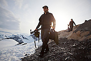 Glaciologists carry equipment to the helicopter landing site above their camp at the Columbia Glacer as they prepare to return to Valdez, Alaska.
