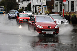 © Licensed to London News Pictures. 11/02/2014<br /> Vehicles driving into flood water in Eynsford High Street as the River Darent has burst its banks in Kent.<br /> The bad weather continues today (11.02.2014) flooding parts of Kent with high winds and more rain to come this week.<br /> Photo credit :Grant Falvey/LNP