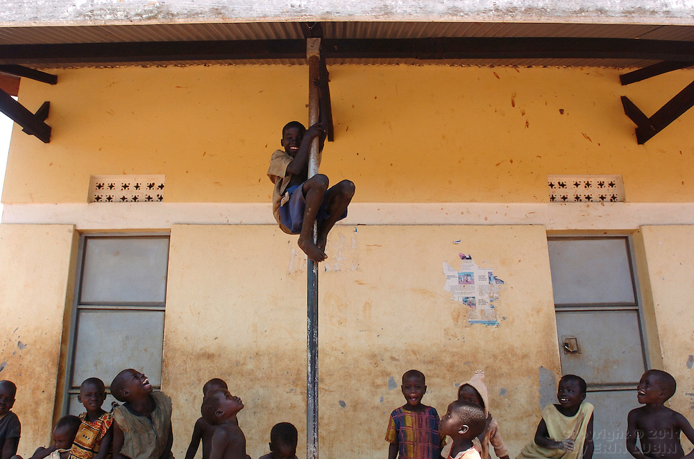 Children play on a building at Tetugu Camp in Gulu District, north Uganda October 7, 2006. Tetugu Camp, with a population of approximately 22,000, is one of 76 camps outside the town of Gulu created for internally displaced people in north Uganda. Since the war began in 1987 over 2 million people have moved from their village homes to camps close to the town of Gulu where they can be protected from the LRA, the Lord's Resistance Army, by the UPDF, the Ugandan People's Defense Force. Over the years the LRA are said to have abducted more than 30,000 children for use as soldiers in their army. The children were often tortured and girls were frequently used as sex slaves. Current peace talks between the Ugandan government and the LRA taking place in Juba, southern Sudan, have the north Ugandan community hoping for an end to the 20 year long war..Photo by Erin Lubin
