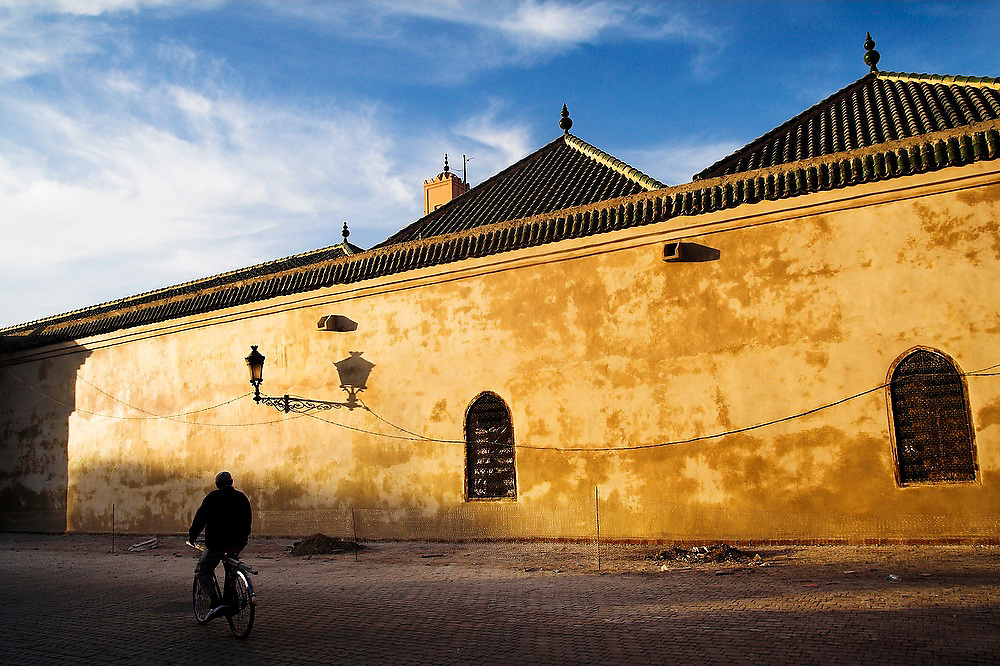 A man rides by on a bicycle outside the Ali Ben Youssef Medersa at sunset in the Marrakech medina, Morocco.