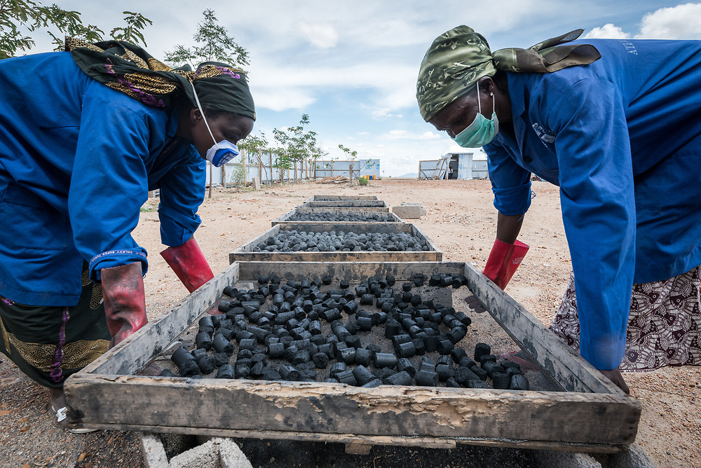 30 May 2019, Mokolo, Cameroon: Aisha Bukar (left) and Hawa Harona (right) place a tray of fresh charcoal briquettes in the sun to dry. At the Minawao camp for Nigerian refugees, degradable and non-degradable waste are separated, so that biomass can be burnt in metal containers, processed and finally transformed into charcoal briquettes as a source of recycled energy to be used as firewood for cooking. With the support of an environment monitor  from the Lutheran World Federation World Service programme, the full process from waste to charcoal is managed and run by the refugees themselves. The Minawao camp for Nigerian refugees, located in the Far North region of Cameroon, hosts some 58,000 refugees from North East Nigeria. The refugees are supported by the Lutheran World Federation, together with a range of partners.