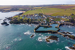 Aerial view of small fishing village and harbour of St Abbs on North Sea coast in Scottish Borders, Scotland, UK