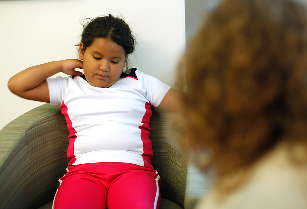 Fernanda Garcia-Villanueva, 8, listens during a counseling session with Marilyn Day (R) Shapedown Program director at The Children's Hospital in Aurora, Colorado July 8, 2010.  Shapedown is part of the child and teen weight management programs at the hospital.  REUTERS/Rick Wilking (UNITED STATES)