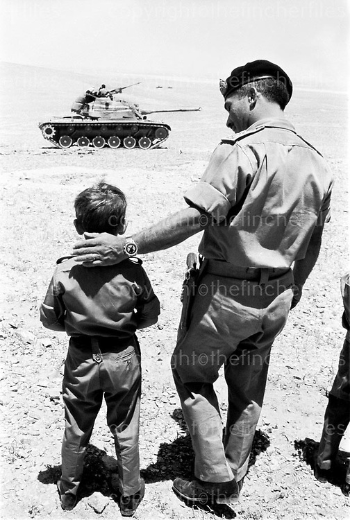 King Hussein of Jordan with his son Prince Abdullah watching an army exercise in the Jordanian desert in 1969. Photograph by Terry Fincher