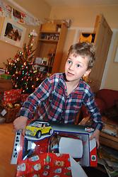 Boy opening Christmas presents on Christmas Day morning; UK