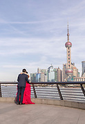 Bride and groom and the futuristic cityscape of Lujiazui skyline from the Bund, Shanghai, China