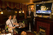 Young couple watch Sarah Palin McCain by life-sized cut-out of Barack Obama after overnight 2008 election London party
