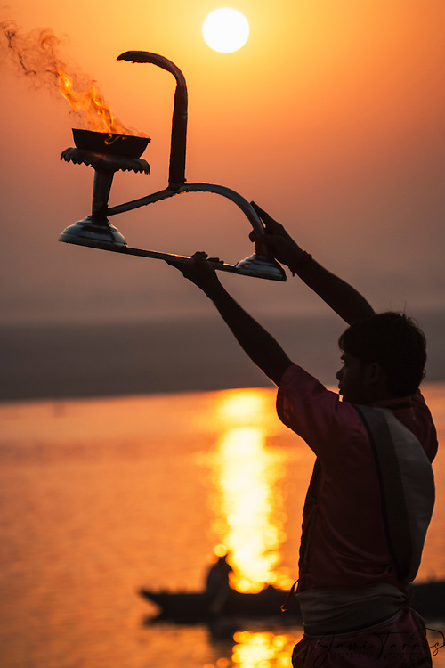 At sunset, a young priest raises his aarti or fire lamp during an evening Ganga Aarti ceremony called the Agni Pooja or Worship to Fire on the main Dasaswamedh Ghat in Varanasi, Varanasi,Uttar Pradesh, India