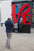 "People interacting with the Love sculpture artwork in the City of London, UK. Robert Indiana's famous ""Love"" sculpture stands at the corner of 99 Bishopsgate – the site of the 1993 IRA bomb 20 years ago."
