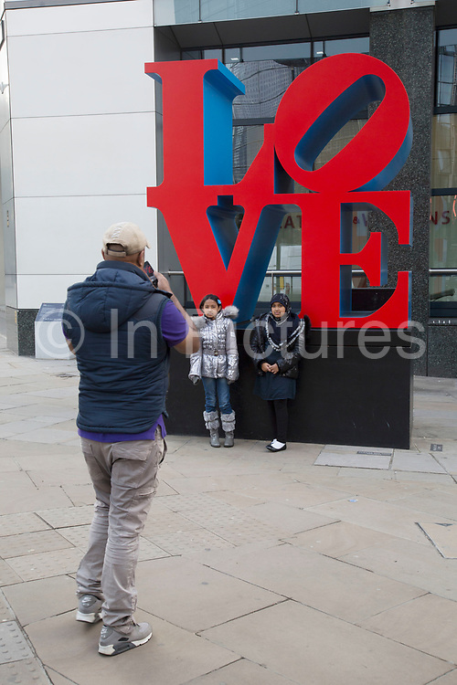 """People interacting with the Love sculpture artwork in the City of London, UK. Robert Indiana's famous """"Love"""" sculpture stands at the corner of 99 Bishopsgate – the site of the 1993 IRA bomb 20 years ago."""
