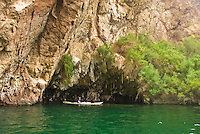 A kayaker explores a mossy cave on The Black Canyon, Nevada.