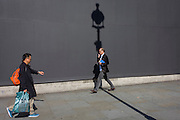 BBC Arts reporter Will Gumperts with a lamp post shadow against a grey construction hoarding in central London's Trafalgar Square.