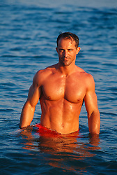 Muscular shirtless man standing waist deep in the ocean