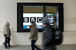© Licensed to London News Pictures. 12/11/2012. London, UK. Members of the public walk past a screen seen through the window of of Broadcasting House in London today (12/11/12). Photo credit: Matt Cetti-Roberts/LNP