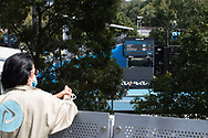 The mother of Australian tennis player Gabriella Da Silvar-Fick, Nuelia Da Silvar-Fick stops on her lockdown walk to watch her daughter play at the 2021 Phillip Island Trophy a lead-up tournament to the Australian Open, from the pedestrian bridge near court 15. A snap lockdown has forced the Australian open to be played with no crowds or supporters for the players.