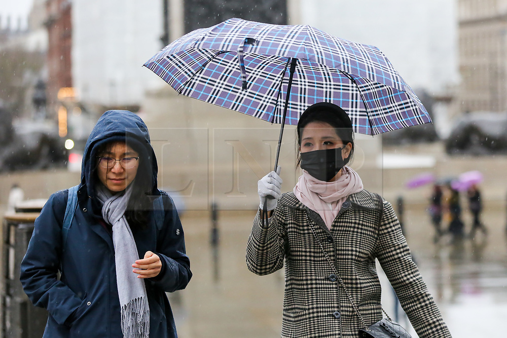 © Licensed to London News Pictures. 15/02/2020. London, UK. A woman wearing a face mask under an umbrella in Trafalgar Square during wet and windy weather as Storm Dennis arrives in London. Heavy rain and strong winds are forecast from today until Monday 17 February as the Storm Dennis sweeps across the UK with heavy rain, gale force winds and flooding. Photo credit: Dinendra Haria/LNP