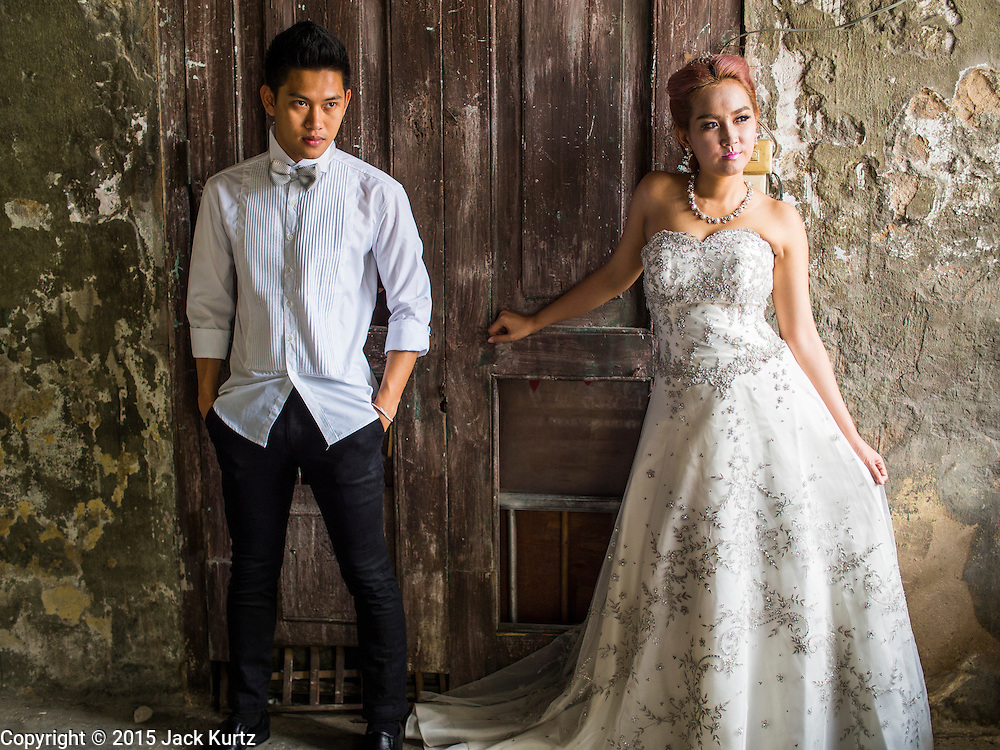 17 MARCH 2015 - BANGKOK, THAILAND: A woman and her fiance pose for prewedding photos in the old Customs House in Bangkok. With its evocative architecture and turn of the century mood, the Customs House is a popular setting for wedding photos and portraits. The old Customs House was once the financial gateway to Thailand (before 1932 called Siam). It was designed by an Italian architect in the 1880s. In the 1950s, customs moved to new, more modern building and the Customs House became the headquarters for the Marine firefighters. The firefighters now live in the decrepit buildings with their families.    PHOTO BY JACK KURTZ