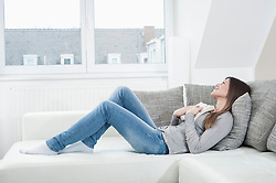 Young woman with opened book lying on couch at home