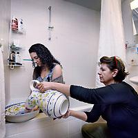 Nederland, Amsterdam , 5 maart 2015.<br /> Suzan Enneking en dochter Anne-Claire in de badkamer van hun appartement aan het Merwedeplein.<br /> Onlangs is legionella geconstateerd in enkele vd woningen vanwege een verouderden defect  warm water systeem.<br /> Vandaar dat, vanuit hygienische redenen het water nu eerst gekookt wordt en handen etc op de ouderwetse manier gewassen worden met lampetkan en bak.<br /> Foto:Jean-Pierre Jans