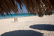 Two people walking on the beach towards the sea, Varadero, Matanzas privince, Cuba.