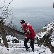 A runner comes up the stairs from Jon's Chapel where he has been down to ring the bell below. Salomon Hammer Trail Winter Edition is a first on Bornholm and is one of the toughest routes in Denmark. The 4 runs consist of a 50 mile run, a marathon, a 1/2 marathon and 10k all run a on an approximate 25km route which includes 860 meter vertical rise on the North East coast of the Danish island Bornholm. The cut-off time for the 50mile run was 16 hours and more than a hundred runners made it to the finishing line. The last runner across the line after 50 miles  was in after 15:14:40
