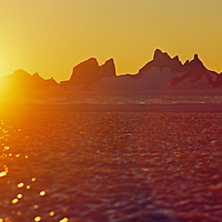 Midnight sun shines over a bare ice glacier & the Fenris Mountains.