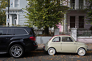 A large 4x4 SUV car parked behind a much smaller FIAT 500 among autumn leaves on Elgin Crescent in Notting Hill, on 7th October 2018, in London, England.