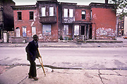 A very poor black man walks through the derelict and burned out remains of houses in a Washington DC. neighbourhood, USA