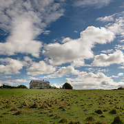 Old farm house in green field with cloudy blue sky
