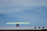 A construction worker carries roofing panels along the pedestrian overpass connecting BART and VTA at the Milpitas BART Station near the Great Mall of the Bay Area in Milpitas, California, on September 2, 2016. (Stan Olszewski/SOSKIphoto)