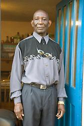Older man standing in the doorway of his house,