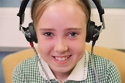 Portrait of young girl wearing headphones taking pure tone audiometry test in aural care centre,