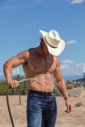 hot muscular cowboy hosing himself off outdoors