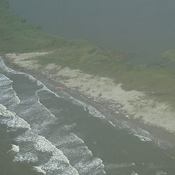 Oil containment booms are washed to the shore away from the marshlands they are designed to protect near the coast of Breton Sound in the Gulf of Mexico off the coast of Louisiana, U.S., on Saturday, May 1, 2010. The BP Plc Deepwater Horizon drilling rig oil spill is threatening the Breton Sound islands that are a habitat for the Louisiana state bird the brown pelican. Photographer: Derick E. Hingle.