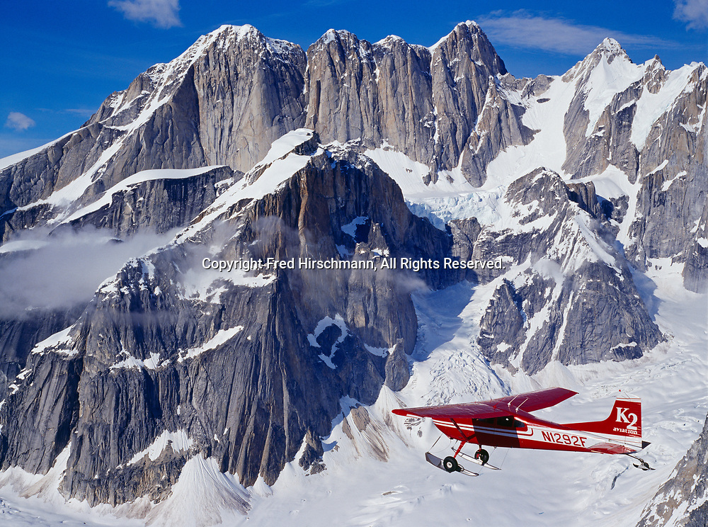 K2 Aviation's Cessna 185 on wheel skis flying up the Ruth Gorge past Mooses Tooth, Denali National Park, Alaska.