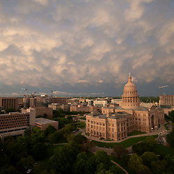 A bank of mammatus clouds follows a rainstorm over the Texas Capitol dome in Austin while a spring weather system blows through central Texas. The mammatocumulus are characterized by cotton-like puffiness and dramatic formations.