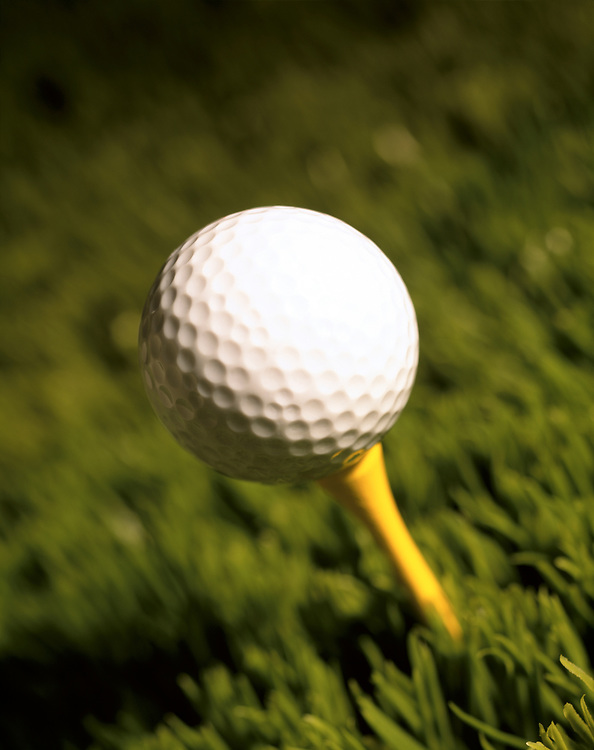 Isolated focus on golf ball on yellow tee in grass